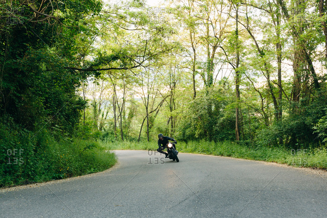 Young male motorcyclist on vintage motorcycle on rural road bend, Florence, Tuscany, Italy