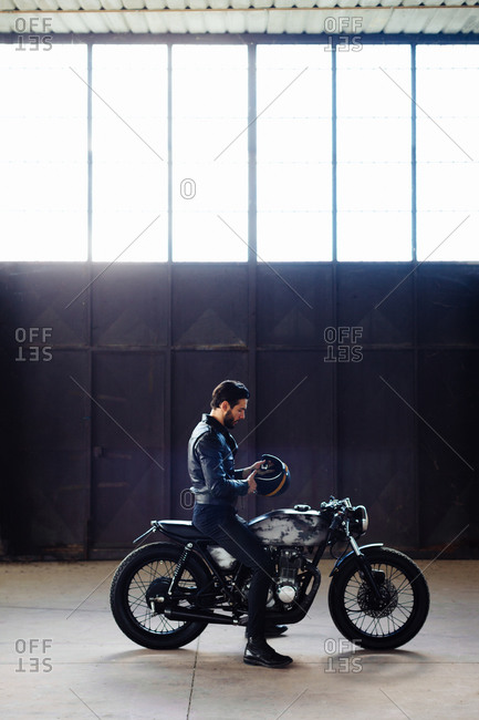 Young male motorcyclist straddling vintage motorcycle in empty warehouse