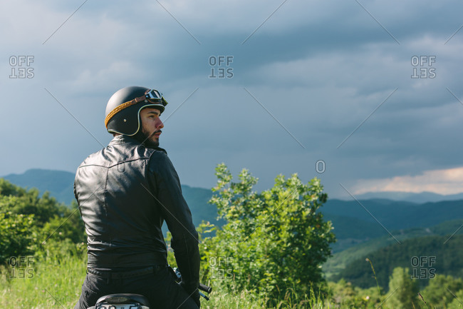 Young male motorcyclist on motorcycle looking over his shoulder, Florence, Tuscany, Italy