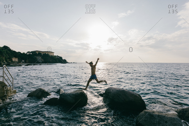 Man jumping from rock to rock in sea