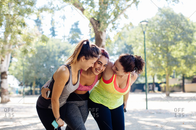 Friends exercising and laughing in park