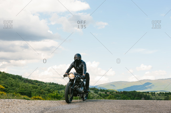 Young male motorcyclist on vintage motorcycle on rural road, Florence, Tuscany, Italy