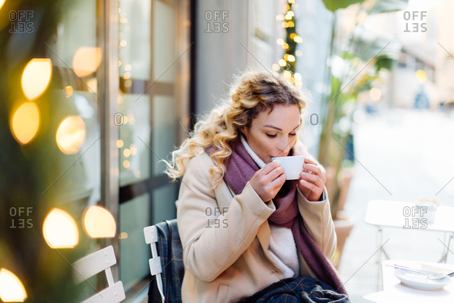Woman having hot drink at cafe, Firenze, Toscana, Italy