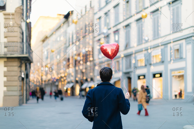 Man with heart shaped balloon at piazza, Firenze, Toscana, Italy