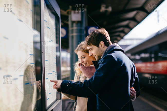 Couple checking schedule at train station, Firenze, Toscana, Italy