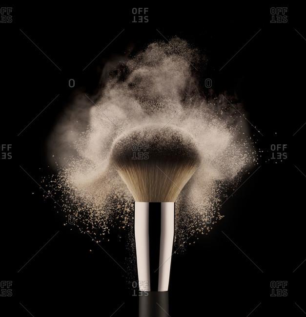 Close up of cosmetic powder brush on black background.
