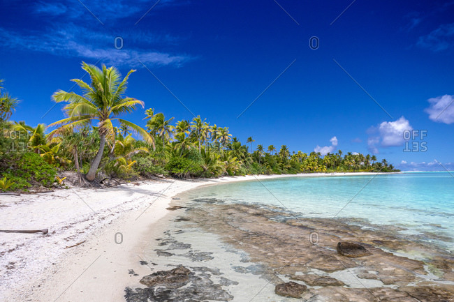 View along a white sand beach at the shoreline, palm trees and clear shallow water