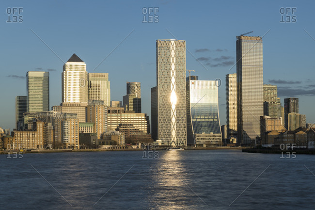 View across the River Thames to tall buildings of Canary Wharf in East London.