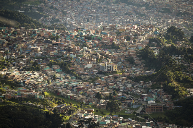 Elevated view of urban settlement, houses on the hillside and valley floor in mountains.