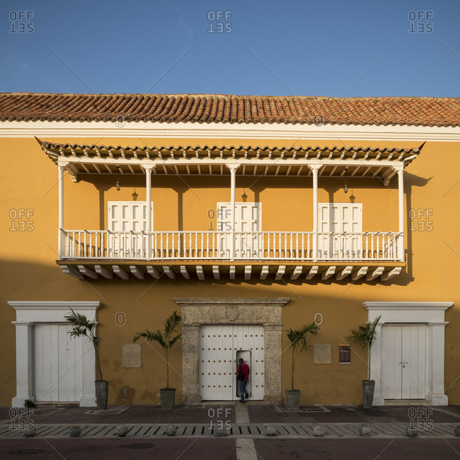 Old City, Cartagena, Bolivar Department, Colombia - January 3, 2020: Facade of historic building in the Old City, painted walls, balcony and shuttered windows and doors.