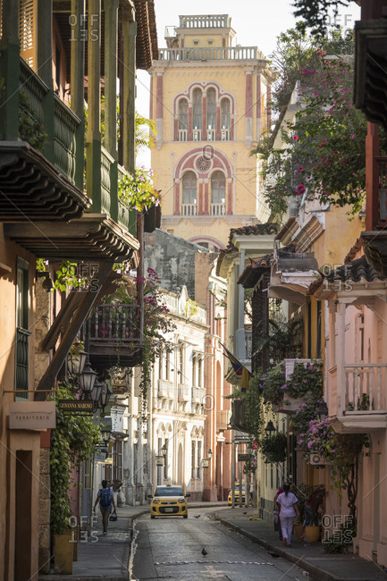 Old City, Cartagena, Bolivar Department, Colombia - January 3, 2020: View along narrow street in the Old City, elegant historic houses with balconies and tall church tower