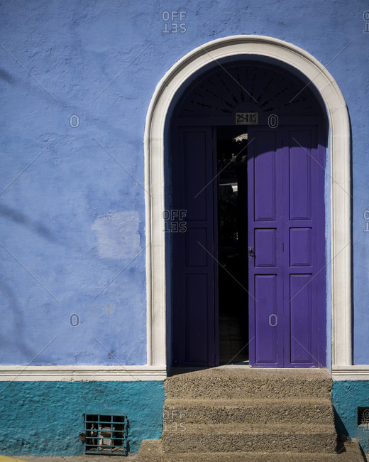 Cartegena, Bolivar Department, Colombia - January 3, 2020: Colorful blue wall and purple painted front door in the Old City, Cartagena