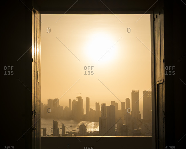 View through a window across the cityscape and seafront with misty orange sky