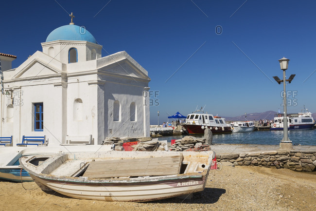 Mykonos Town, Mykonos , Greece - April 28, 2016: Beached fishing boats and traditional Greek Orthodox church.
