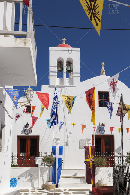 Mykonos Town, Mykonos, Greece - April 28, 2016: Greek Orthodox church and colorful flags hanging over narrow alley in Mykonos Town.