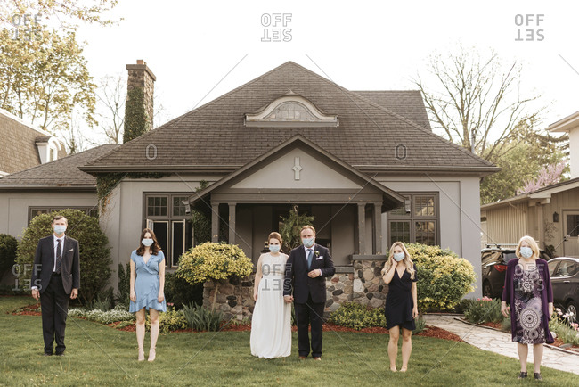 Wedding party posing for group portrait on front lawn, wearing face masks during Coronavirus crises.