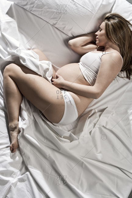 Portrait of heavily pregnant woman lying on bed, cradling stomach.