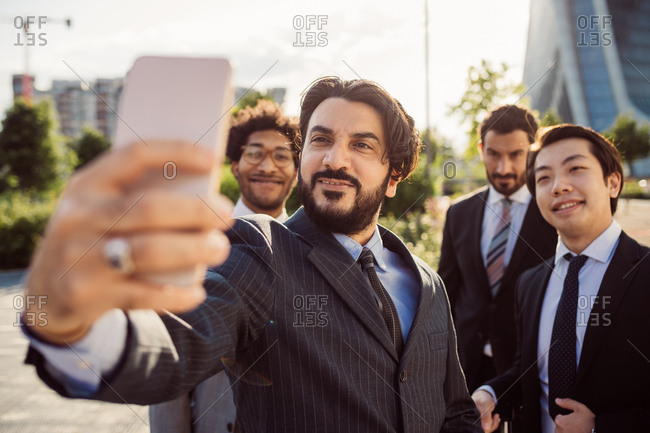 Mixed race group of businessmen hanging out together in town, taking selfie with mobile phone.