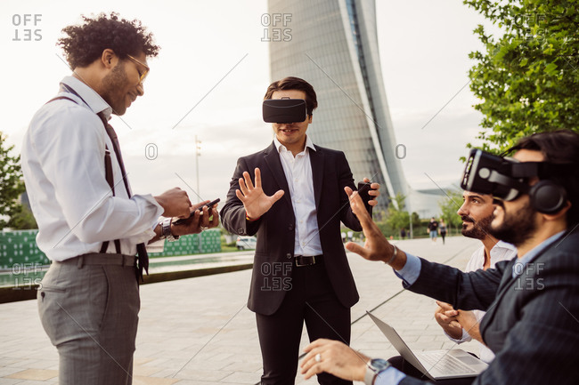 Mixed race group of businessmen hanging out together in town, wearing VR headsets.