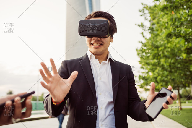 Portrait of Asian businessman wearing VR headset.