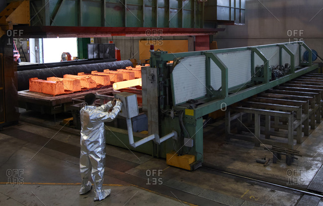 Man wearing silver heat-protective suit working in a steel factory.