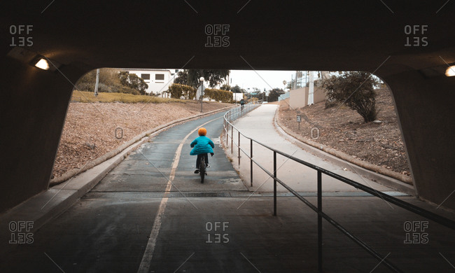 Rear view of boy cycling through cycle path tunnel.