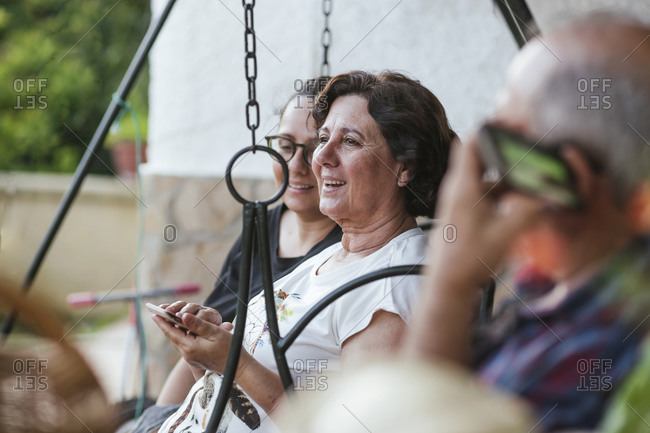 Grandparents using smartphone- sitting on canopy swing
