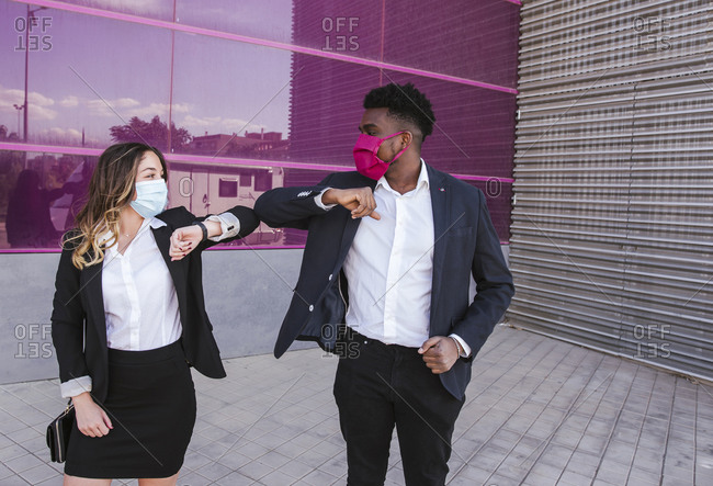 Business people wearing masks giving elbow bump while standing against modern building