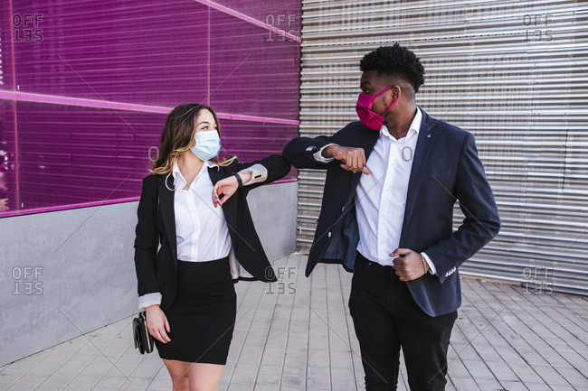 Business people wearing masks giving elbow bump while standing against building in city
