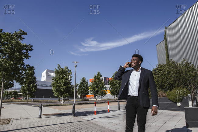 Cheerful businessman talking over smart phone while standing in city during sunny day