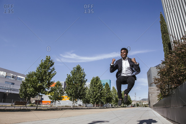 Cheerful male professional jumping on footpath against blue sky in city during sunny day