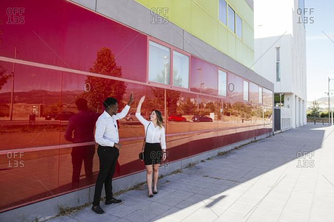 Business professionals giving high five while standing by red wall in city