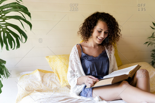 Happy young woman reading book while sitting on bed in log cabin