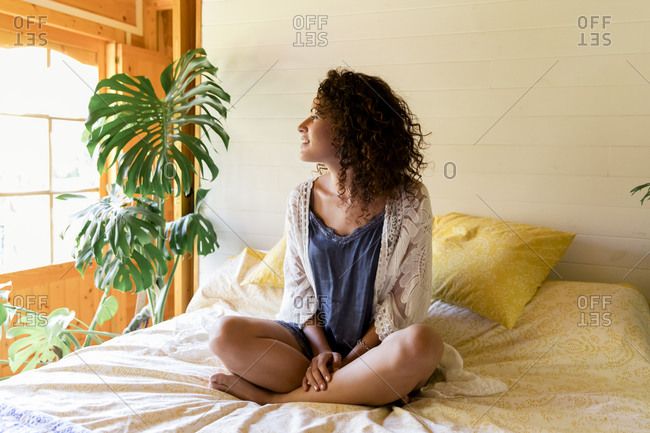 Relaxed young woman sitting on bed in log cabin