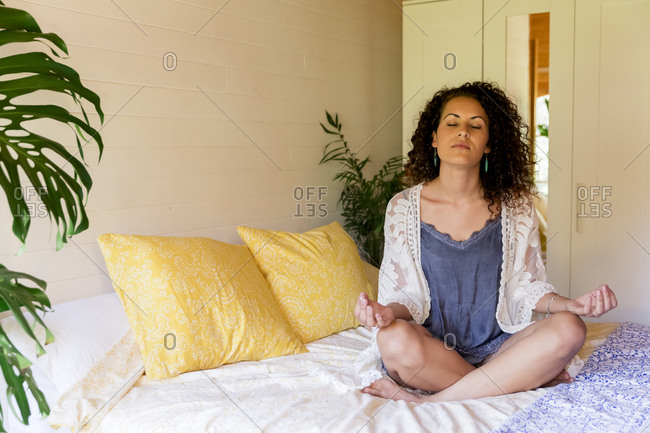 Relaxed young woman meditating while sitting on bed in log cabin