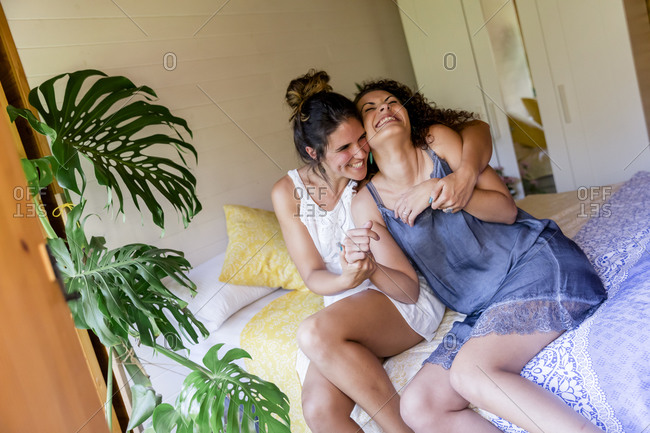 Cheerful woman embracing female friend while sitting on bed in cottage