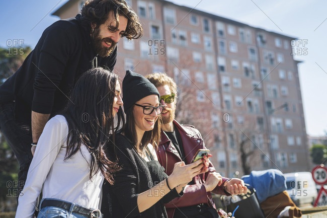 Friends looking at smart phone being used by young woman in city