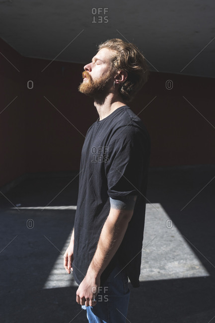 Bearded man with eyes closed standing against built structure on sunny day