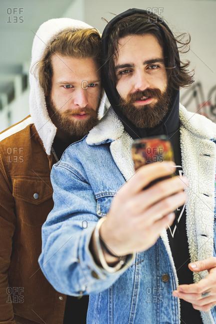 Handsome male friends wearing hood taking selfie with smart phone