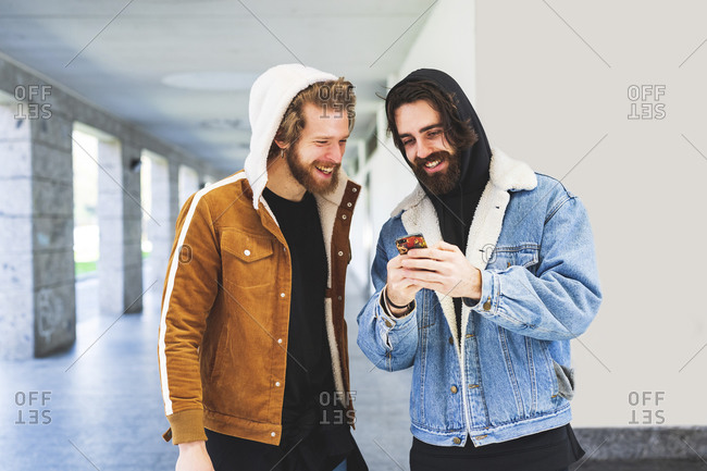 Young man showing smart phone to male friend while standing against wall