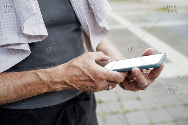 Close-up of senior man using mobile phone while standing outdoors