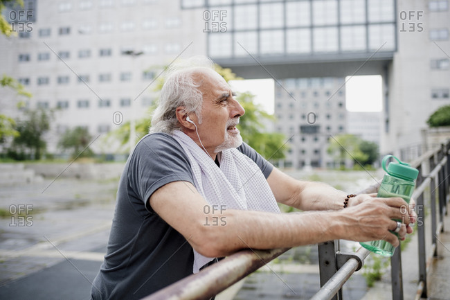 Senior man holding water bottle listening music while standing by railing