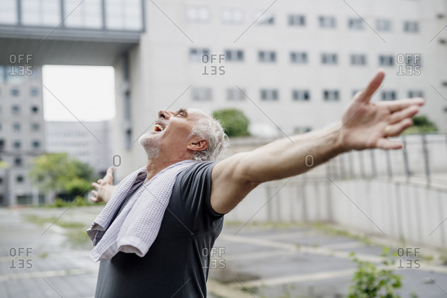 Cheerful senior man with arms outstretched standing against building in city