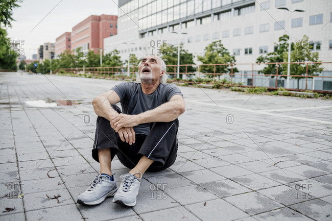 Tired senior man with mouth open looking up while sitting on footpath in city