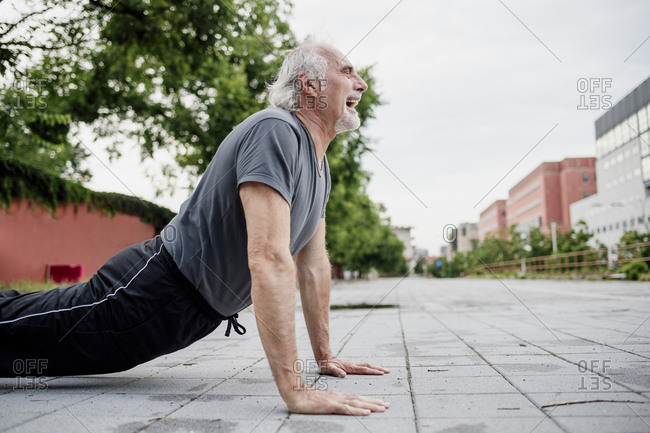 Senior man with mouth open doing push-ups on footpath in city