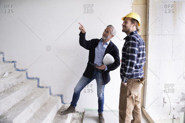 Male architect guiding construction worker while standing on steps in renovating house