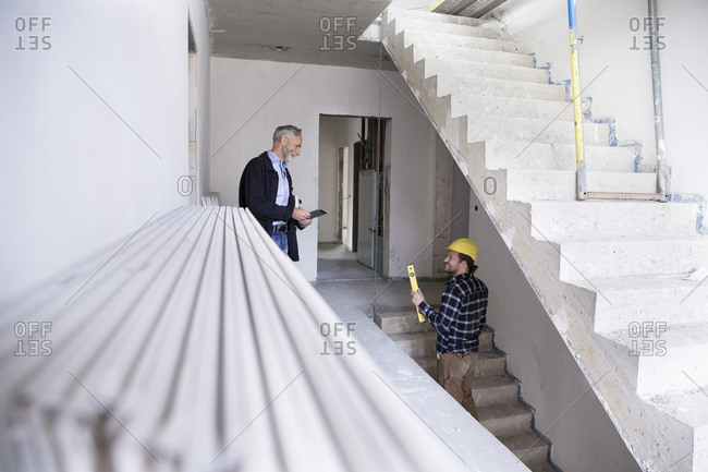 Architect and construction worker discussing while standing in constructing house