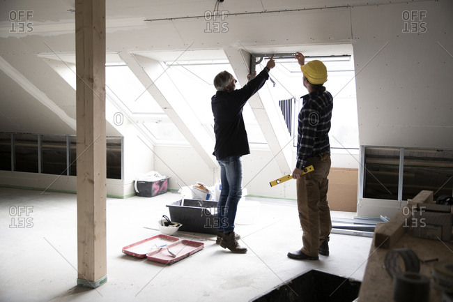 Architect and construction worker discussing about window frame in renovating house