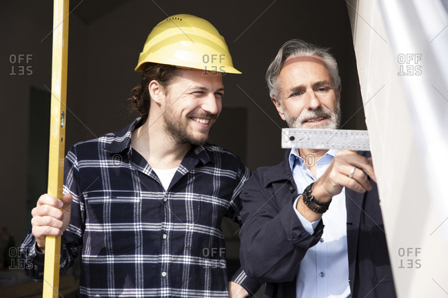 Smiling construction worker looking at measurement showing by architect in constructing house seen through window