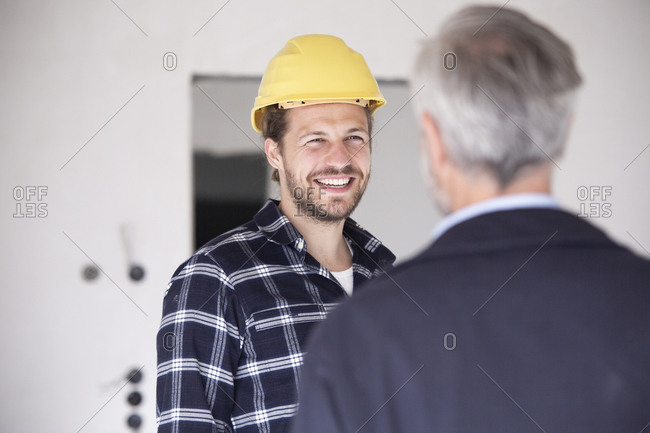 Smiling construction worker wearing hardhat talking with architect in constructing home